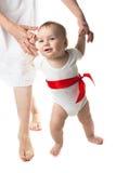 Se tenir de marche de bébé remet la mère, fond blanc Images libres de droits