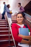 Se tenir femelle de sourire réserve avec des étudiants sur des escaliers dans l'université Image libre de droits