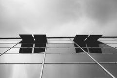 Se upp den glass fasaden av en modern byggnad med glass fönster öppna för luft Royaltyfri Fotografi