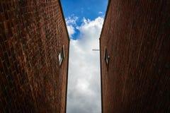 Se upp, en sikt av himlen, mellan två tegelstenväggar Royaltyfri Foto