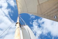 Se upp masten på en segla yacht som fokuseras på flaggan på mastheaden royaltyfria bilder