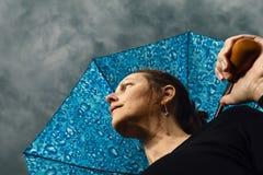 Se upp på en kvinna som rymmer ett paraply och moln Arkivfoto