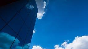 Se upp på entäckt skyskrapa och att reflektera blå himmel- och bortgångmolnen stock video