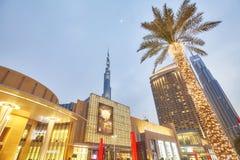 Se upp sikt av den upplysta palmträd-, Dubai galleria- och Burj Khalifa fasaden på skymning Royaltyfri Fotografi