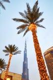 Se upp sikt av den upplysta palmträd-, Dubai galleria- och Burj Khalifa fasaden på skymning Arkivbild