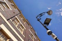 Se upp till himlen med tegelstenbyggnad på det vänstert och gatan royaltyfria foton