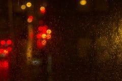 Se ut mitt fönster på en regnig natt i staden Arkivfoton