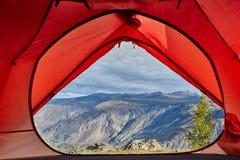 Se ut ur öppen tältdörr på den lugna floden royaltyfri fotografi