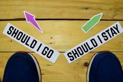Se vado o dovrei restare i segnali di direzione opposti con le scarpe da tennis su di legno fotografie stock