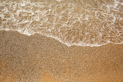 Sea ​​caresses the sand on the beach Royalty Free Stock Photo
