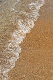 Sea ​​caresses the sand on the beach Stock Photos