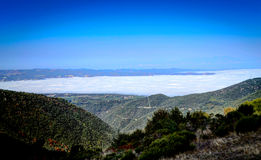 Sea of ​​clouds below the mountain Stock Image