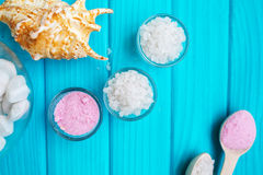 Sea salt in a glass white stones and Shell for spa and relaxation on a blue background Stock Images