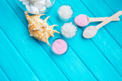 Sea ​​salt in a glass white stones and Shell for spa and relaxation on a blue background Royalty Free Stock Photo