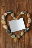Sea ​​stones in a heart shape. With a card on a dark wooden background Stock Image