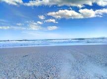 Sea surf sky sand sand beach. Sandy beach surf of the sea wave and the blue sky and a few clouds. Surf of the sea to a sandy beach Royalty Free Stock Photos