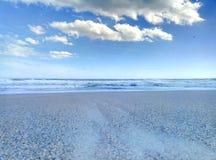 Sea surf sky sand sand beach. Sandy beach surf of the sea wave and the blue sky and a few clouds. Surf of the sea to a sandy beach Stock Photo