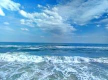 Sea surf sky sand sand beach. Sandy beach surf of the sea wave and the blue sky and a few clouds. Surf of the sea to a sandy beach Royalty Free Stock Photography