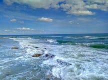 Sea surf sky sand sand beach. Sandy beach surf of the sea wave and the blue sky and a few clouds. Surf of the sea to a sandy beach Stock Images