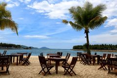 Sea ​​view, restaurant, tables, sea, palms, Vietnam, tropics. View of the sea from a restaurant surrounded by coconut trees in Vietnam Royalty Free Stock Photos