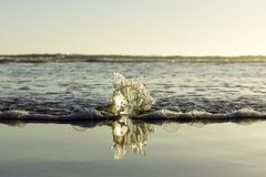 Sea water breaking on glass sphere on the beach stock image