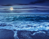 Sea ​​waves crashing on sandy beach at night. Green and mighty sea wave attacks the sandy beach and break on them at night in full moon light Royalty Free Stock Image