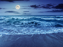 Sea waves running on sandy beach at night. Green and mighty sea wave craches on sandy beach and break at night in full moon light royalty free stock photos