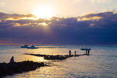 Sea fishing at sunset. Fishermen catch fish at sunset. Boat bobs on the waves Royalty Free Stock Photos