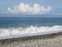 Sea. Cloud, blue sky and shingle Stock Image