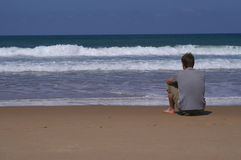 By the sea. Young man, sitting by the sea Stock Image