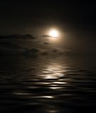 At the sea. Night landscape at the sea. The moon is reflected in dark water. A photomontage Royalty Free Stock Image