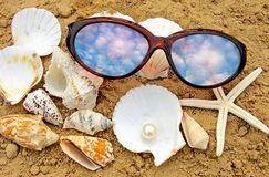 On sea. Sea, pearls sinks and sunglasses Royalty Free Stock Photos