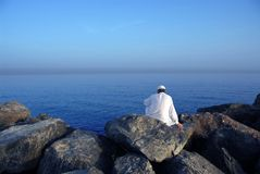 Sea. A man sitting on the rock near sea Stock Photo