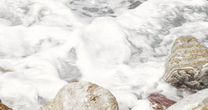 Sea abstract detail close-up rocks at the beach splashed by waves creating loads of sea foam – Sea Abstract Background stock video footage