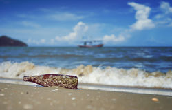 Sea acorn colony on a brown glass bottle dumped pollute at the sand beach,blurred splash of sea wave and blue sky in background. Filtered image,selective focus Stock Photo