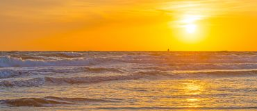 Sea along a sandy beach in the light of sunset. In summer Royalty Free Stock Photos