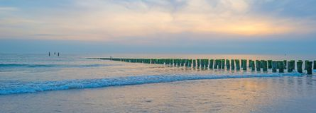 Sea along a sandy beach in the light of sunset. In summer Stock Images