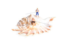 Sea angling. Tiny figures of anglers with fishing rods on a seashell isolated on white stock images