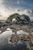 Ballintoy Sea Arch. This is the sea arch at Ballintoy on the north coast of Ireland. This was taken at low tide leaving tidel pools reflecting the sky royalty free stock photos