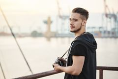 Sea attracts this photographer. Outdoor portrait of attractive young guy standing in harbour, enjoying looking at sea royalty free stock image