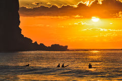Sea Avalon Cliff 4 surfers Orange. A group of active surfers floating on open ocean waves at sunrise agaist orange sun off Avalon beach in a shade of tall Royalty Free Stock Photos