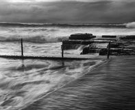 Sea Avalon Pool triangles BW. Black-white image of rock pool fragment at Avalon beach in SYdney. Severe stormy weather and strong waves overflow pool borders Royalty Free Stock Photos