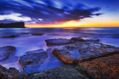 Sea Avalon Rocks Blue Rise. Dark blue hour sunrise over sea horizon at Avalon beach rocks with alga of Sydney Northern beaches Royalty Free Stock Image