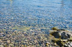Sea background, ripple surface of transparent water. Seascape background, ripple surface of transparent water, view of colorful stones bottom underwater stock photos