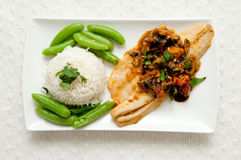 Sea bass. Mediterranean sea bass with heirloom tomatoes and garlic plus white rice and snap peas Royalty Free Stock Image