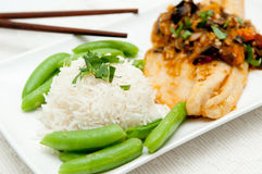 Sea bass. Mediterranean sea bass with heirloom tomatoes and garlic plus white rice and snap peas Royalty Free Stock Photography