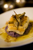 Sea bass on a bed of purple potato puree. Baked sea bass on a bed of purple potato puree topped with roasted artichoke quarters and cauliflower carpaccio Royalty Free Stock Photography