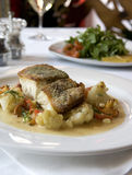 Sea Bass with Cauliflower. Photographs of a grilled sea bass with cauliflower on a white plate on a white table cloth stock image