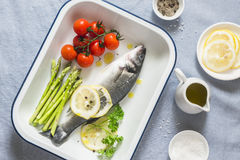 Sea bass, cherry tomatoes and asparagus in the baking tray. Raw ingredients for cooking lunch. On a blue background Royalty Free Stock Photography