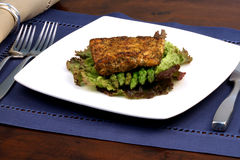 Sea bass dinner. Delicious grilled sea bass, seasoned with fine spices with asparagus and lettuce bed royalty free stock images